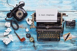 old typewriter with name typed on paper D. Earl Stephens. Blue colored distressed wood background, smoke pipe and rolled up paper